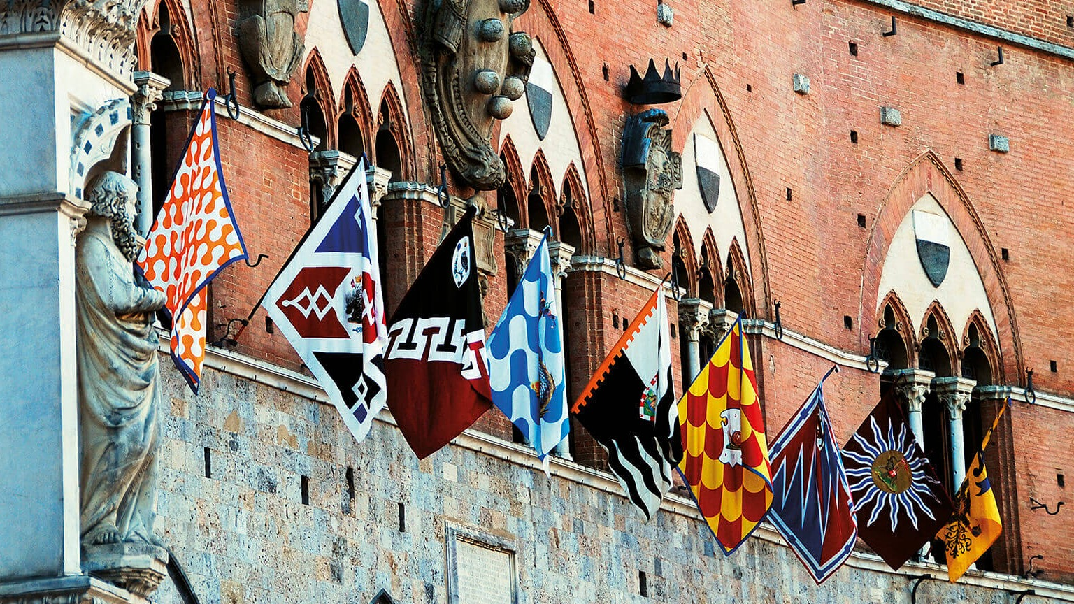 Colourful flags at the Palio di Siena adorning historic building