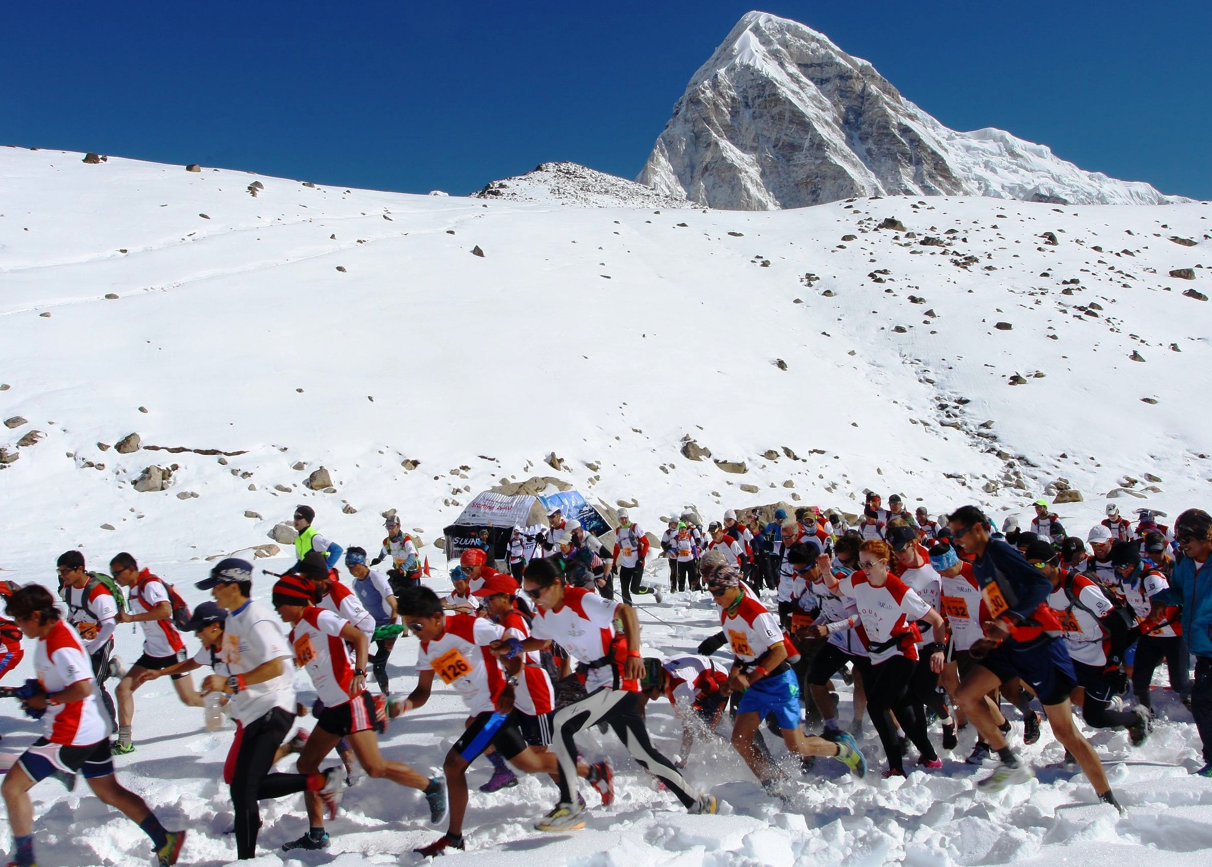 Runners with snowy mountain behind in Everest Marathon