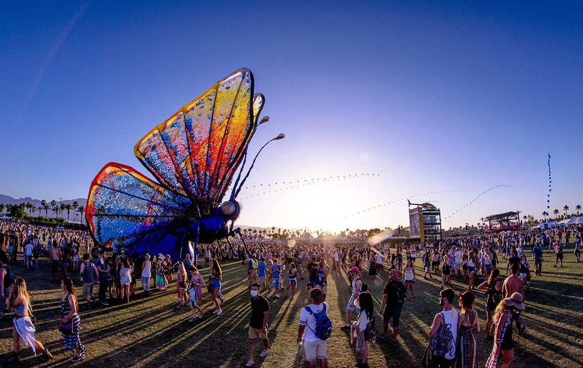 butterfly sculpture and crowds at Coachella festival