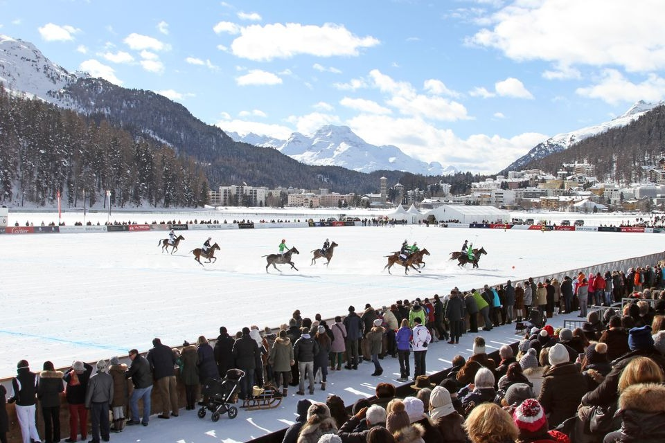 Crowds and snow polo players and horses at Snow Polo World Cup with St Moritz mountains behind