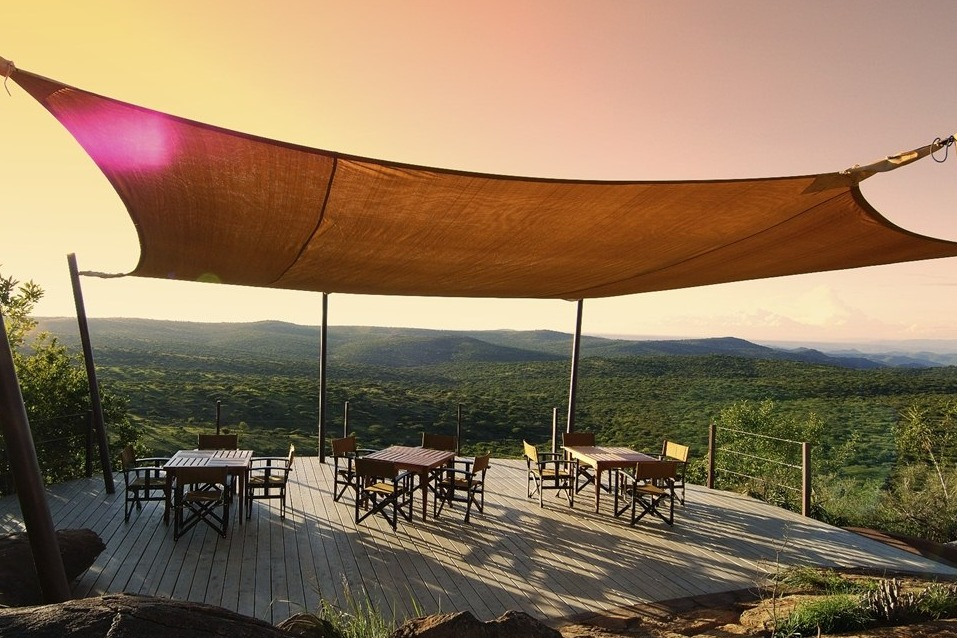 Ol Lentille tables and chairs in the sun overlooking the forest canopy