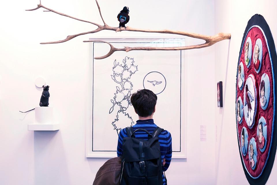 Visitor looking at art at London Art Fair