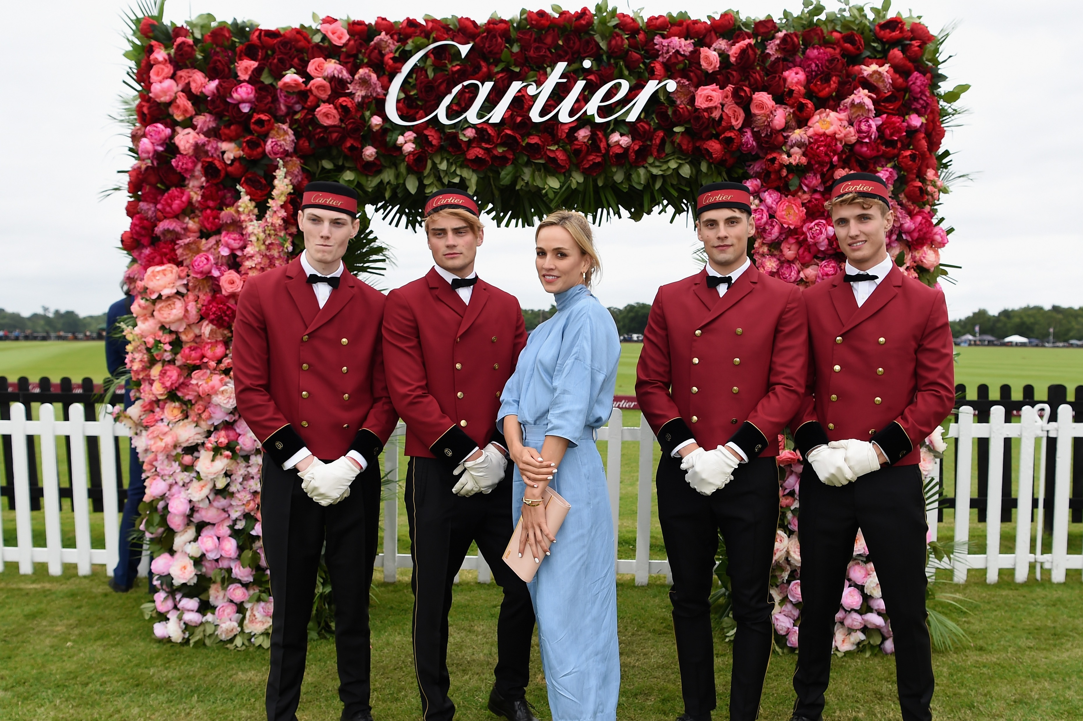 cartier queen's cup models posing in front of Cartier flower display