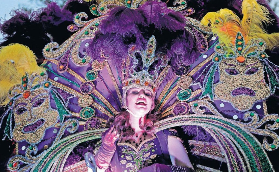 New Orleans Mardi Gras performer in amazing purple and green feathered costume