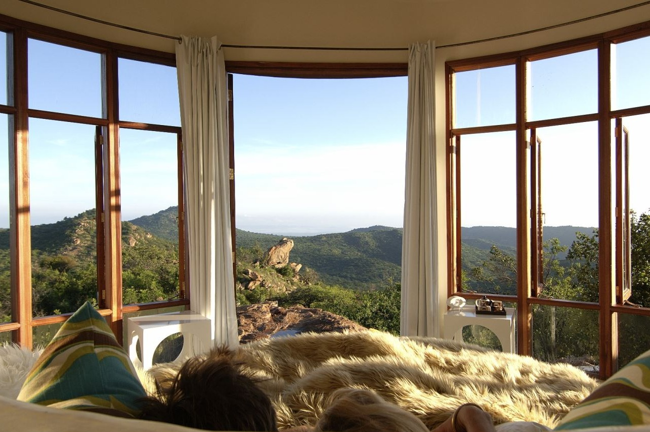 couple at ol lentille enjoying the wilderness view from curved windows