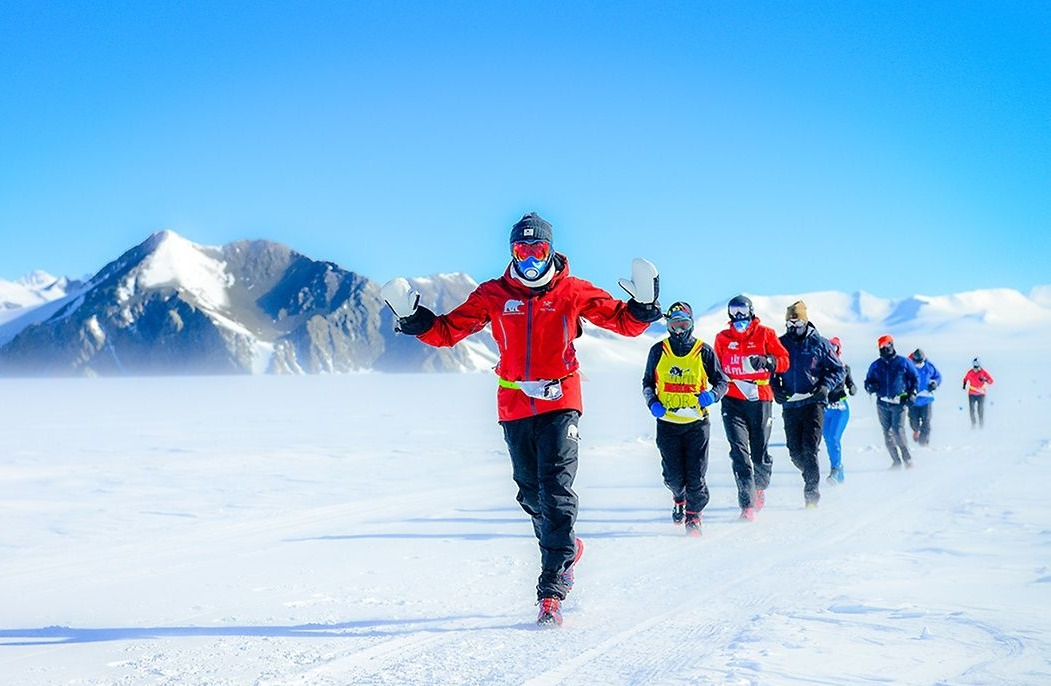 runners in snow with mountains at antarctic ice marathon