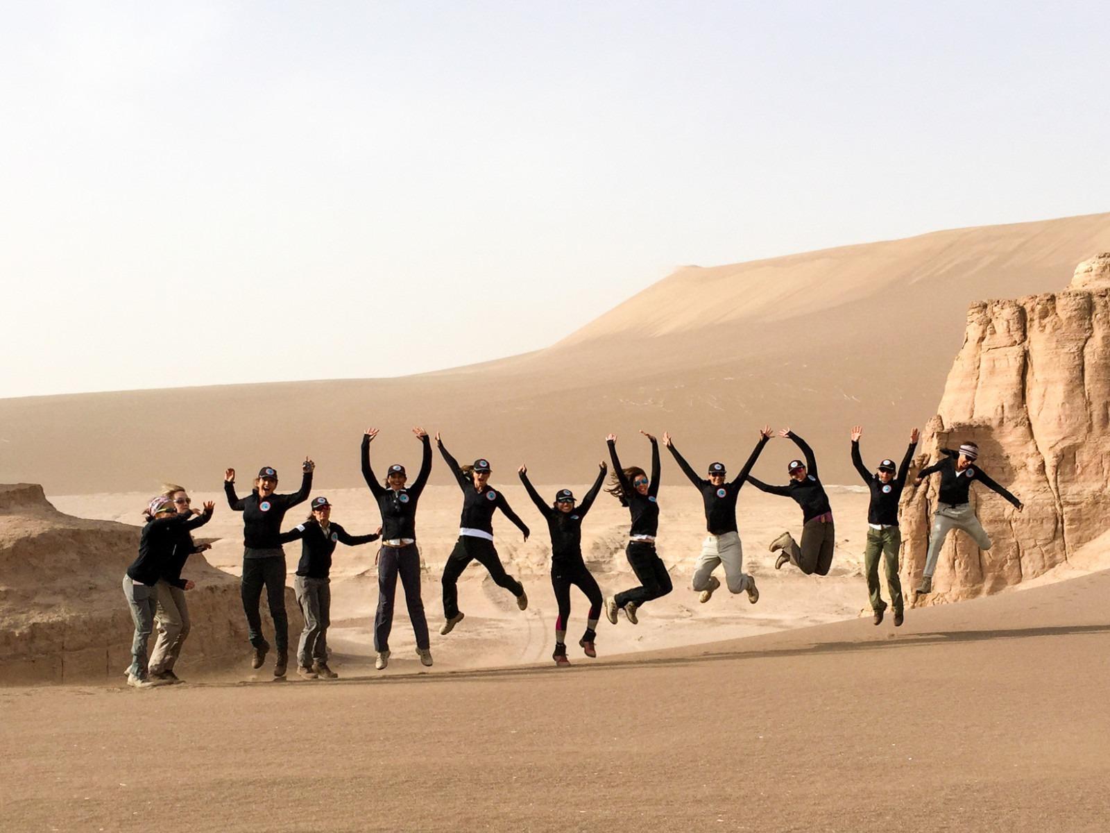 group jumping in air on iranian desert trek