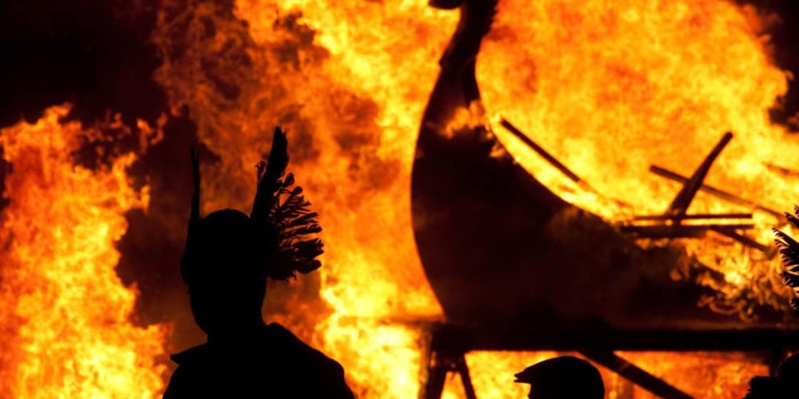Fire and shadows of Viking longship and warrior at Up Helly Aa