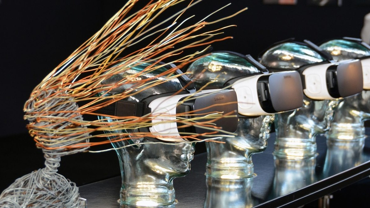 Sculptures or virtual reality masks and a figure with hair made from wires blowing in the wind at London Art Fair