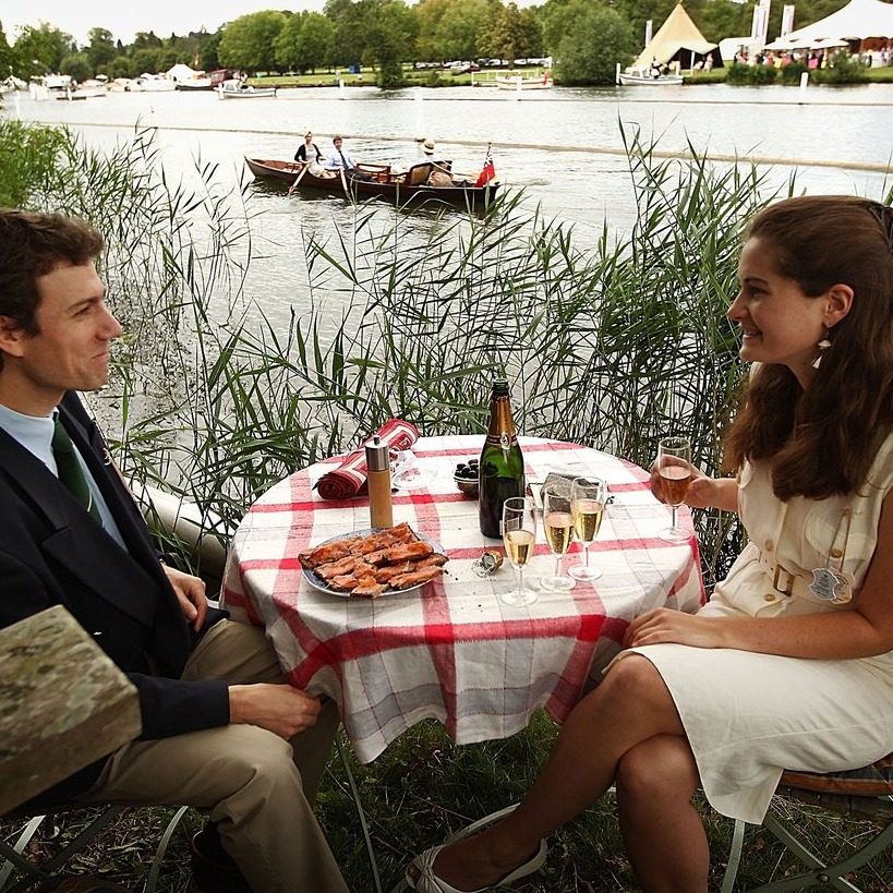 couple at table with champagne next to river with rowers in background at Henley Regatta
