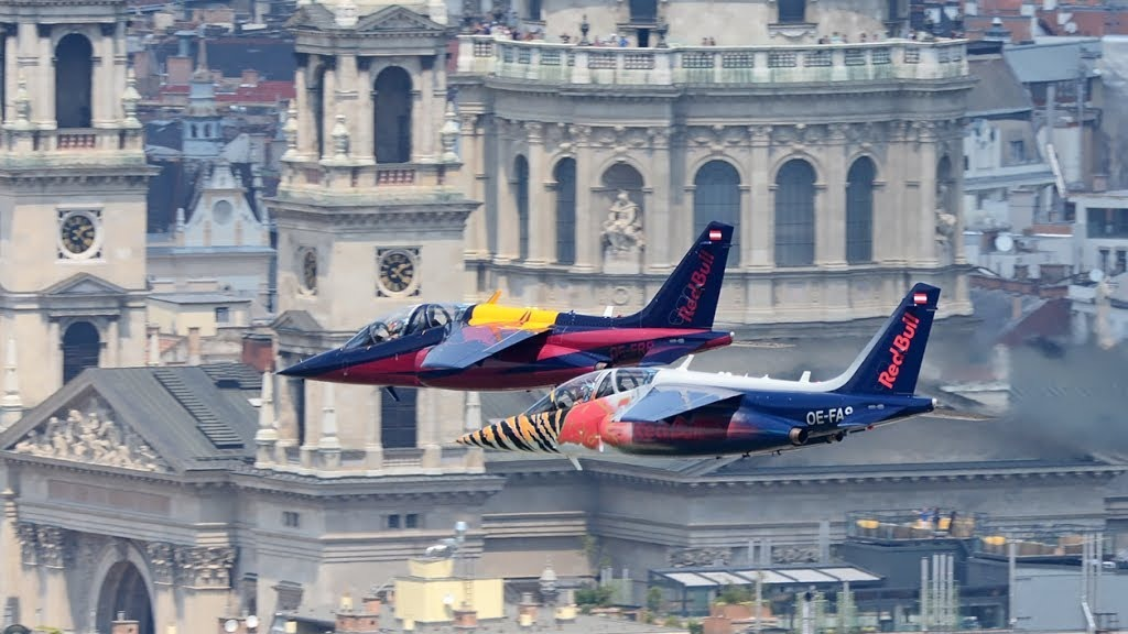 Red Bull air race planes flying in front of Budapest buildings