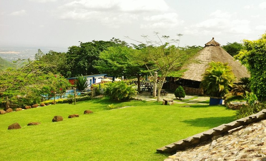Hillburi mountain retreat with green grass and grass topped round huts
