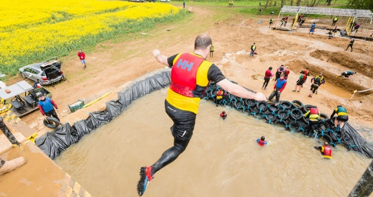 Rat Race Dirty Weekend competitor jumping into water obstacle