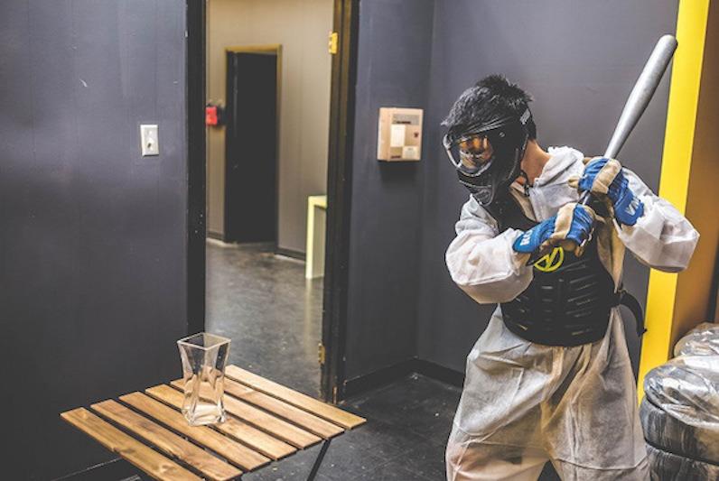 Man prepares to break vase with baseball bat at The Smash Room