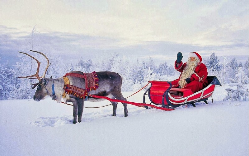 Father Christmas in a sleigh pulled by a reindeer as part of Spend Christmas at Santa's Lapland