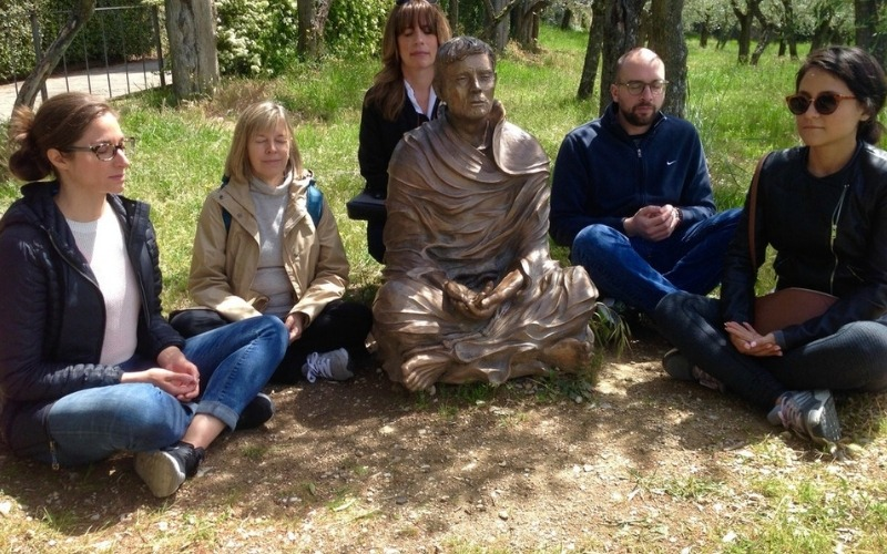 People meditating with a statue on 6 Day Meditation Retreat to Assisi