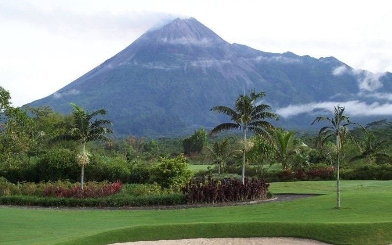 merapi golf course with palm trees and mountain behind
