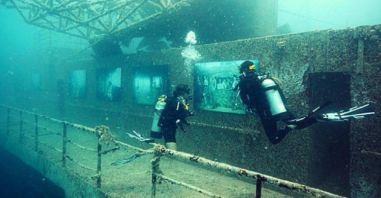 Divers at sea inspecting ship at bottom of ocean