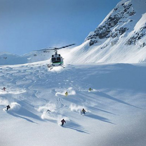 People skiing off-piste down a mountain with a helicopter above them - Heli-Skiing Kamchatka