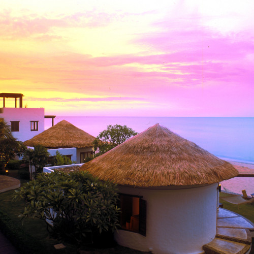 Sunset over luxury huts at Aleenta Hua Hin Pranburri Resort