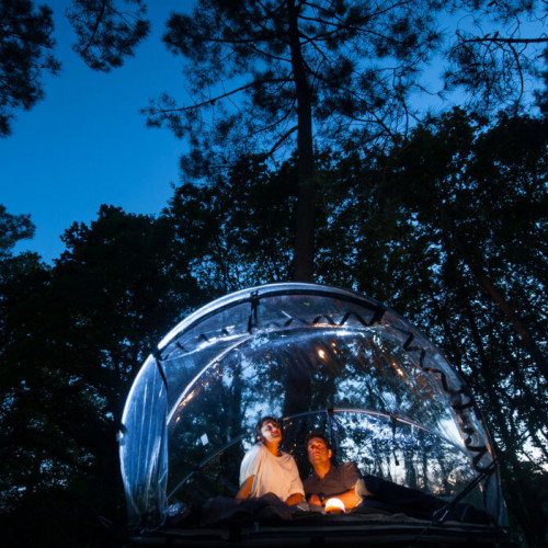 Couple in bubble at night in forest at Buubble hotel, Iceland