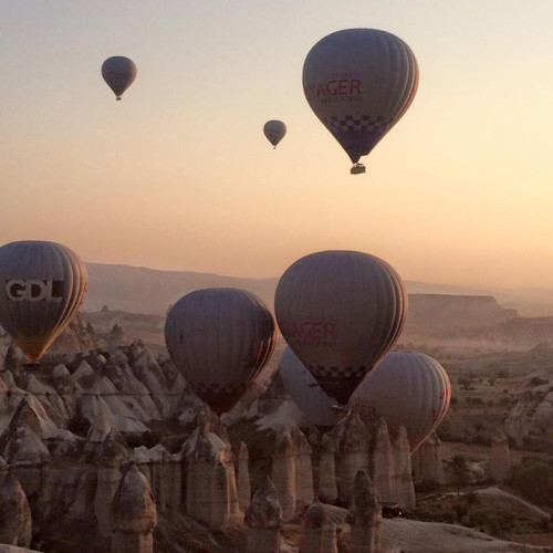 hot air balloons flying over Cappadocia at sunrise