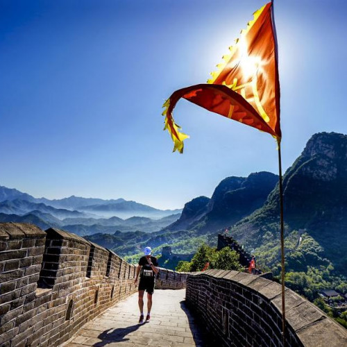 Marathon runner on great wall of china with mountain views and flag