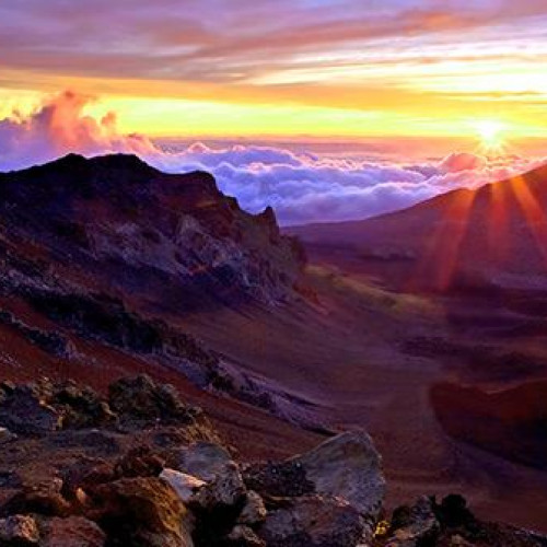 Colourful sunrise behind mountains on haleakala sunrise tour