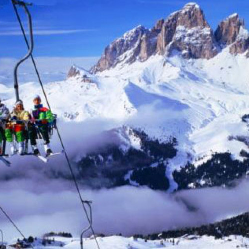 Skiers on a ski lift in the Dolomites