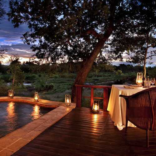 Swimming pool with lanterns on the decking on a treehouse penthouse and African safari