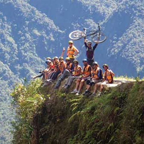 Group of cyclists sitting on edge of cliff with bike leader holding up bike above his head behind them on the Death Road, Bolivia