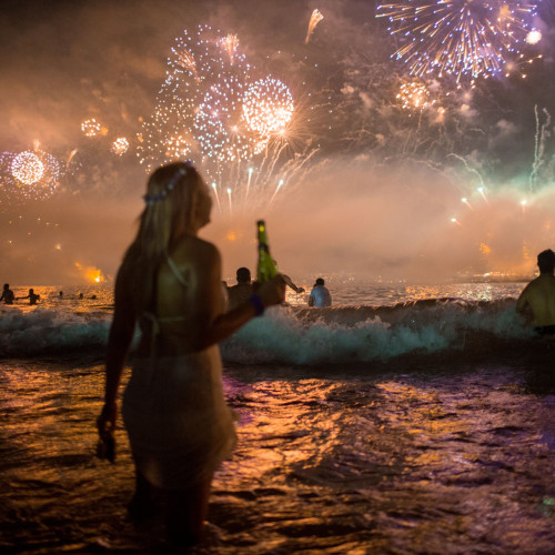 Partygoer on copacabana beach and new year fireworks