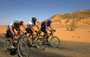 Cyclists riding through the African desert on Tour D'Afrique
