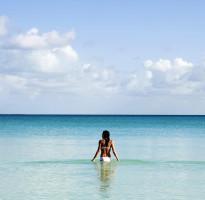 woman in bikini standing in the ocean on vamizi island paradise
