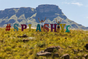 #SPLASHY coloured letters with people posing by them and mountains in the background t Splashy Fen
