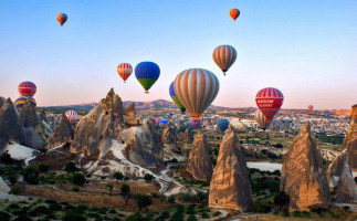 brightly coloured hot air balloons flying over fairy chimneys in Cappadocia