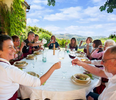 group raising glasses at al fresco dinner table in tuscan sun