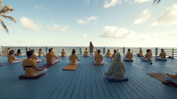 group practising yoga by the sea at sivananda yoga retreat
