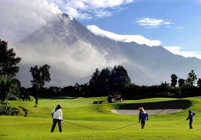 people playing golf at merapi golf resort with mountain in clouds behind