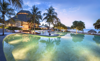 swimming pool and bungalow surrounded by palm trees lit up in evening light at Mukul Resort, Nicaragua
