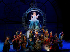 Actor playing Belinda the Good witch surrounded by villagers on stage in Wicked the Musical