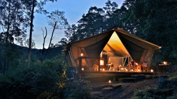 Glamping luxury wooden hut lit up at night in Baumurru Plains