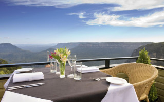 Table set on edge of decking with stunning views of the Katoomba Blue Mountains at the Echo Hotel