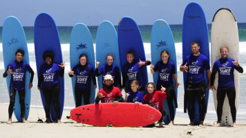 Line of surf students with surfboards behind them posing for photograph at Margaret River Surf School