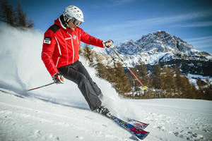 Man in red jacket skiing down mountain in the Dolomites