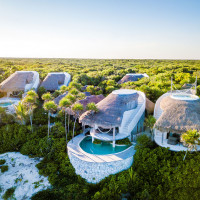 unusual round white huts nestled into the rainforest with swimming pools and rush roofs at Papaya Playa Project