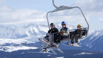 Skiers on chairlift over Tyrol mountains