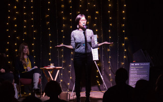 Storyteller on stage at The Moth StorySLAM