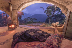 Enchanted cave accommodation with rustic bed, fire and open sided room with views of the blue mountains