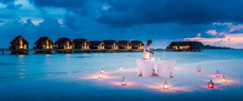 romantic table set as night time on beach with beach huts behind at Como Cocoa Island